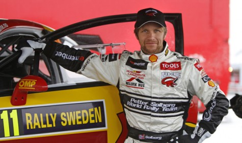 Petter Solberg stands next to his Citroen rally car